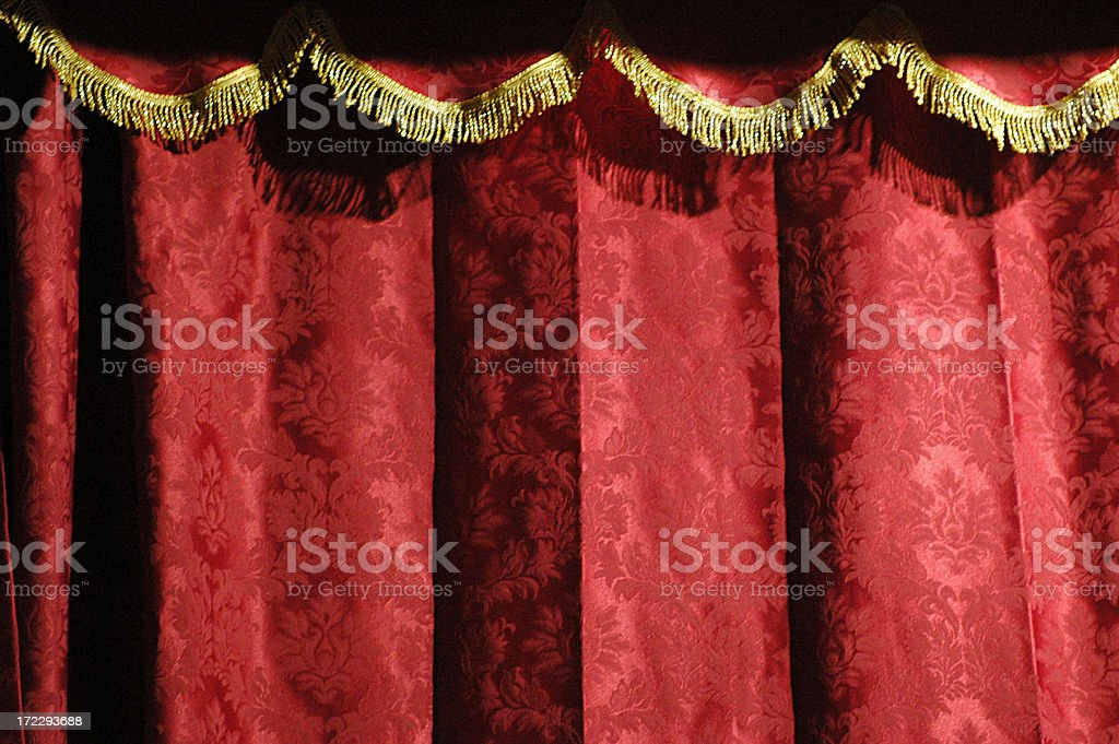 Close-up of a theater's red curtain with gold accents stock photo