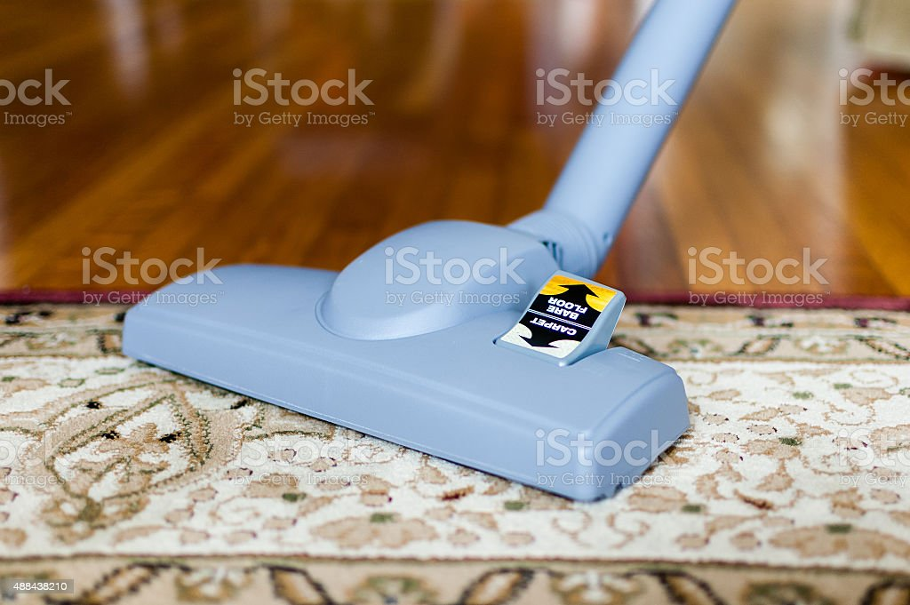 Close-up of a vacuum cleaner on an oriental rug stock photo