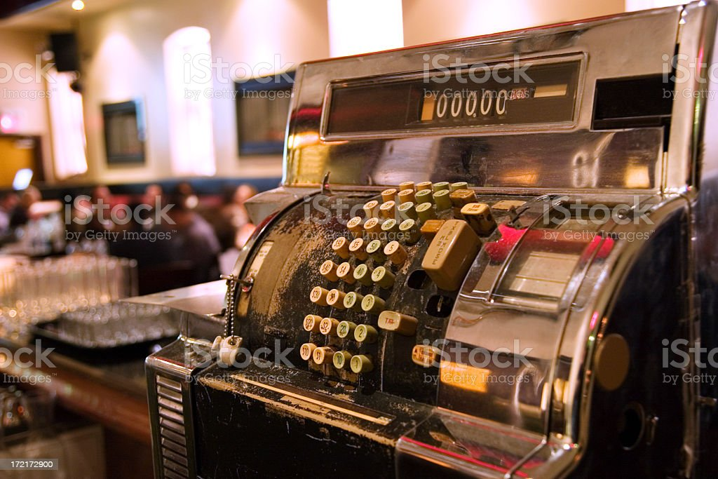 Close-up of a vintage chrome cash register behind a bar royalty-free stock photo