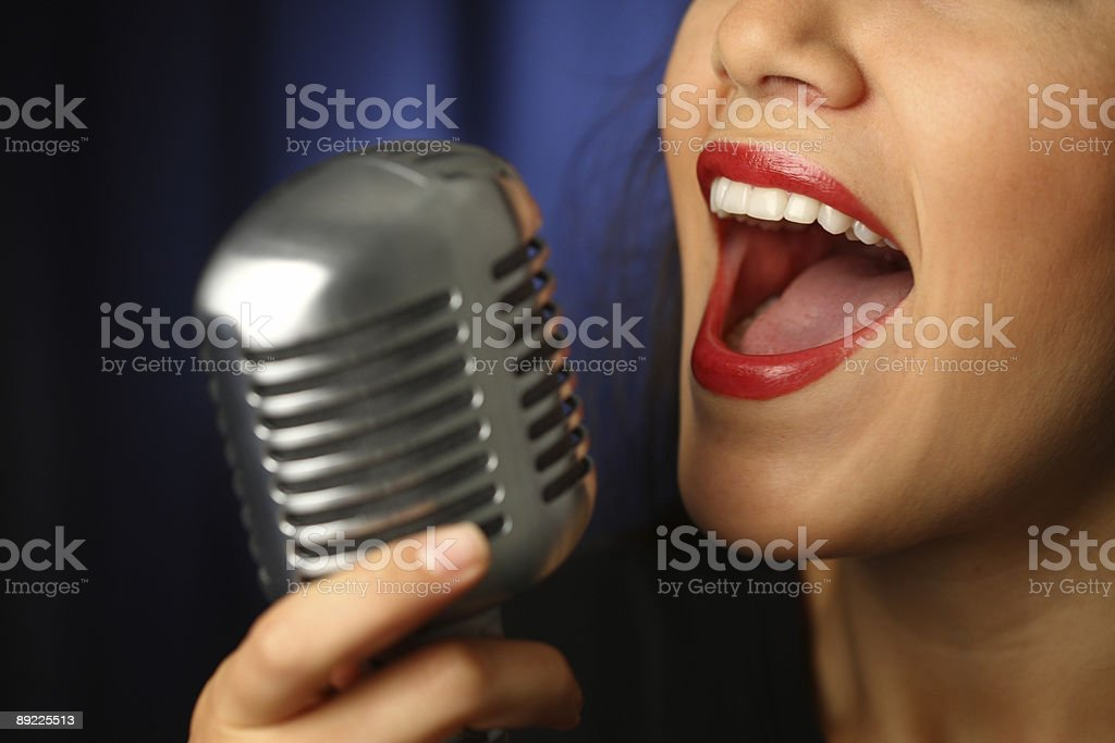 A close-up of a vintage microphone with a singing woman stock photo