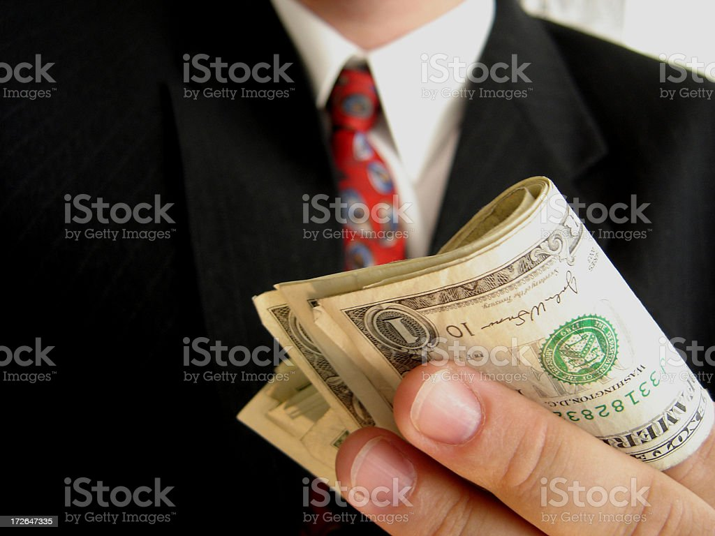 Close-up of a wad of money being held by a businessman stock photo
