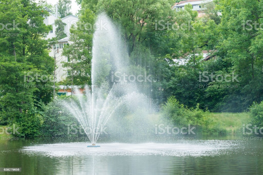 Closeup of a water fountain in the middle of a lake stock photo