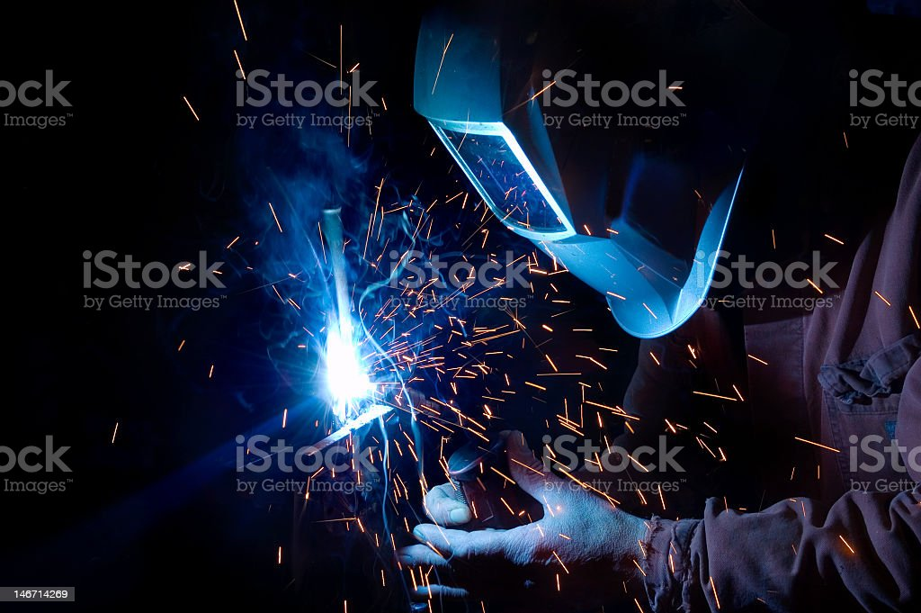 Close-up of a welder in uniform creating blue sparks royalty-free stock photo