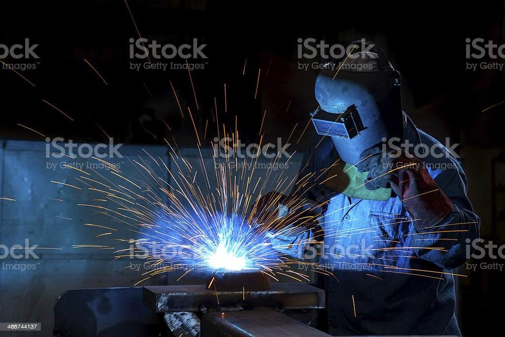 Close-up of a welder wielding sparks stock photo