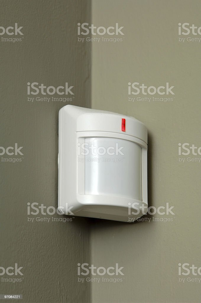 Close-up of a white motion detector on a gray wall stock photo