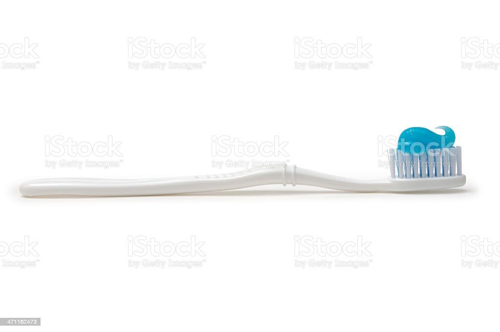 A close-up of a white toothbrush with blue toothpaste on it stock photo