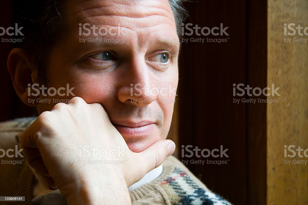 Close-up of a wistful man with hand on his chin looking away royalty-free stock photo