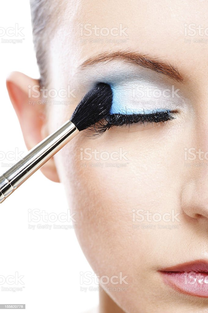 A close-up of a woman applying blusher eyelid stock photo