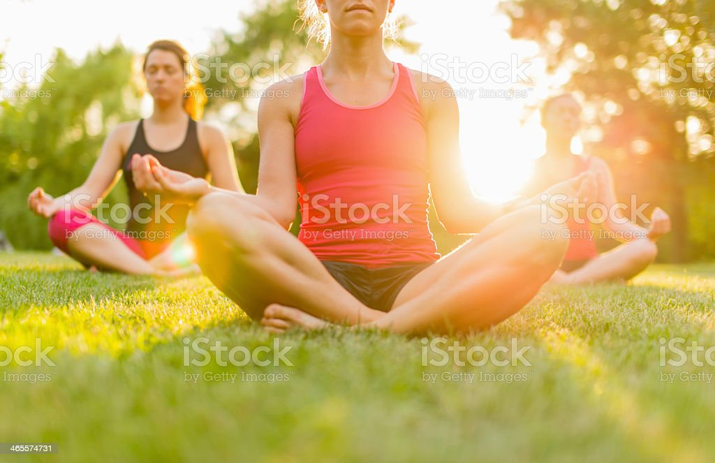 A closeup of a woman doing yoga outside with two other women stock photo