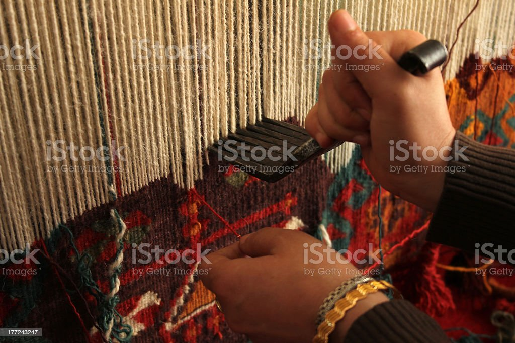 Close-up of a woman hand-weaving a colorful rug stock photo