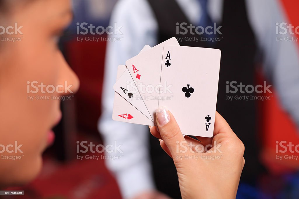 Close-up of a woman holding Four Aces. stock photo