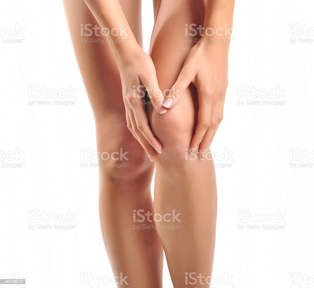 Close-up of a woman holding her knee, as if in pain stock photo