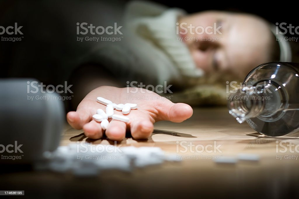 A close-up of a woman holding pills trying to commit suicide stock photo