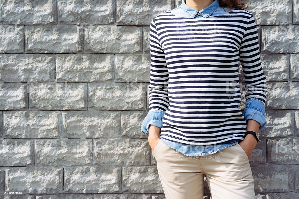 Close-up of a woman in a denim shirt, striped t-shirt stock photo