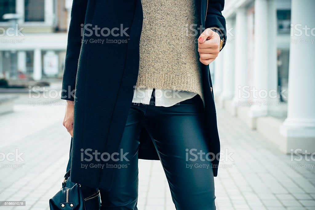 Close-up of a woman in a sweater, coat, black pants stock photo