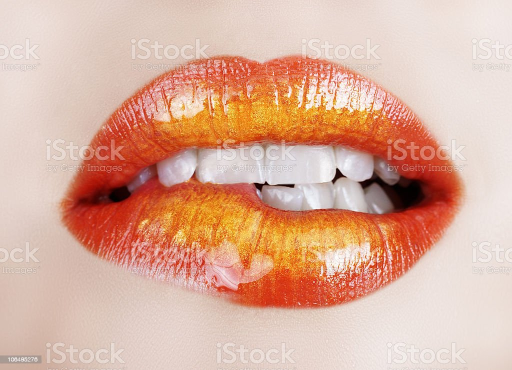 Closeup of a woman in red lipstick biting her bottom lip royalty-free stock photo