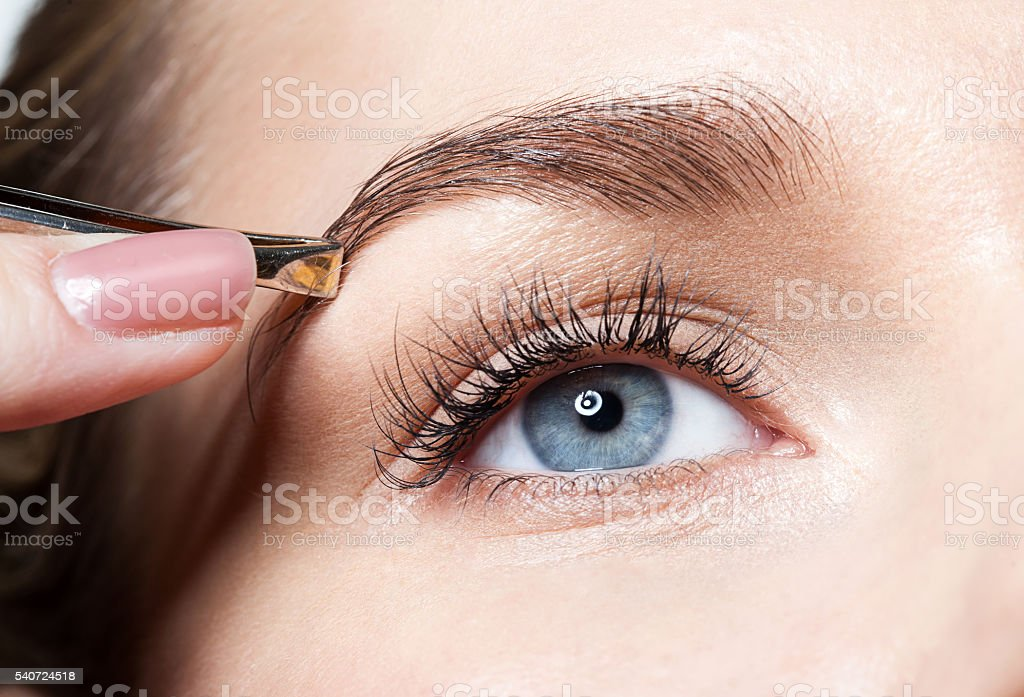 Closeup of a woman pulls out her eyebrows with tweezers stock photo