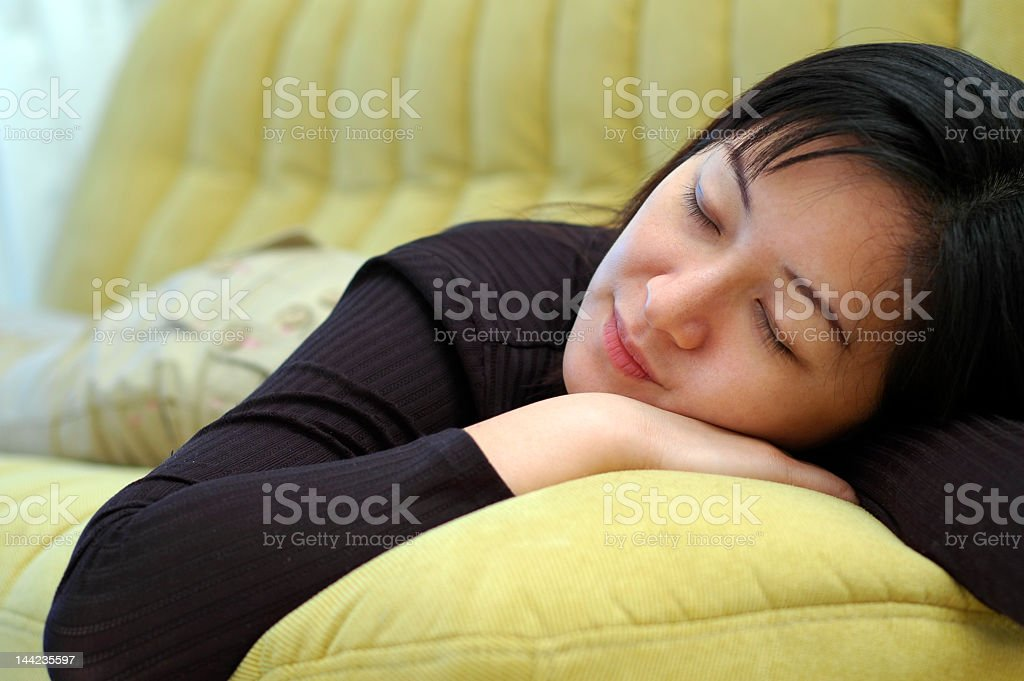Closeup of a woman sleeping on a large yellow cushion royalty-free stock photo