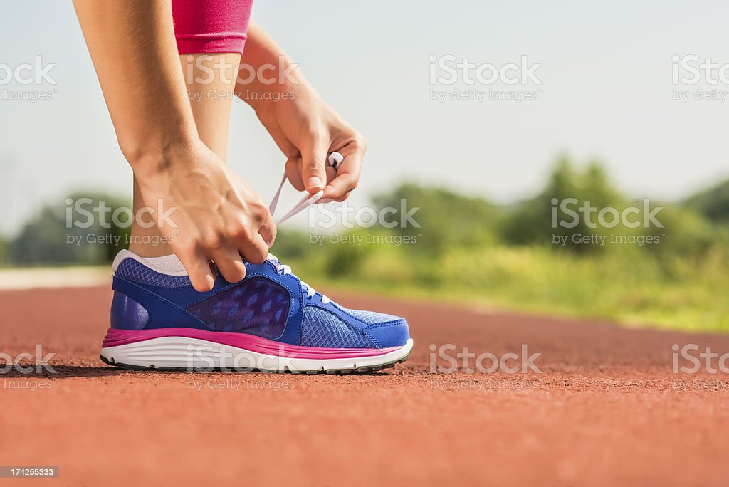 Close-up of a woman tying up her running shoes' laces royalty-free stock photo