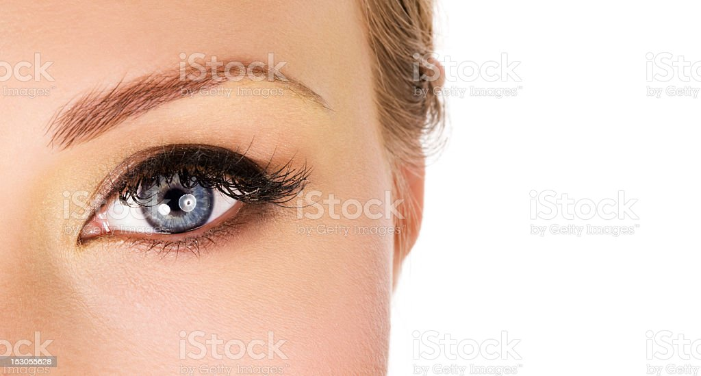 A close-up of a woman's blue eye and shaped eyebrow royalty-free stock photo
