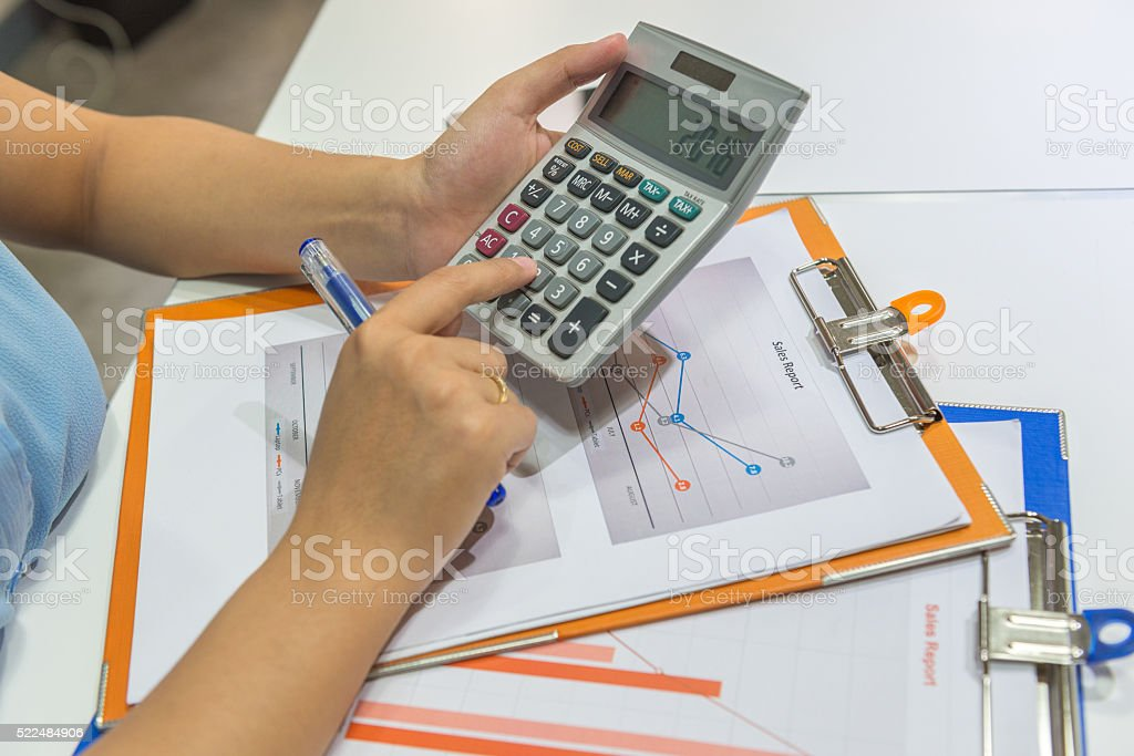 Close-up of a woman's hand on a calculator stock photo
