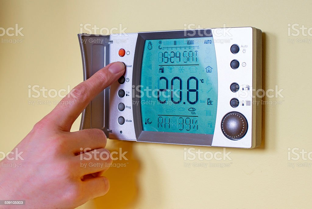 Closeup of a woman's hand setting the room temperature stock photo