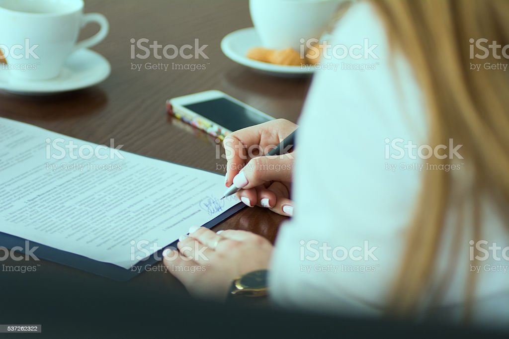Close-up of a woman's hand signed paper document at office stock photo
