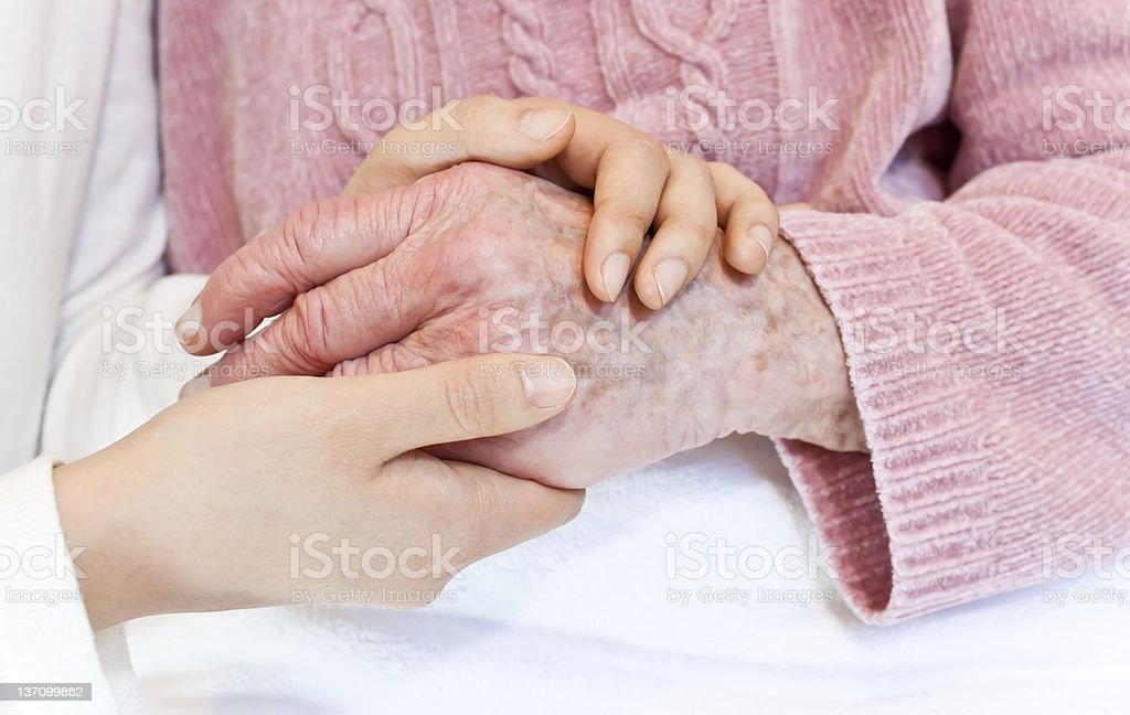 Close-up of a woman's hands holding an elderly woman's hand royalty-free stock photo