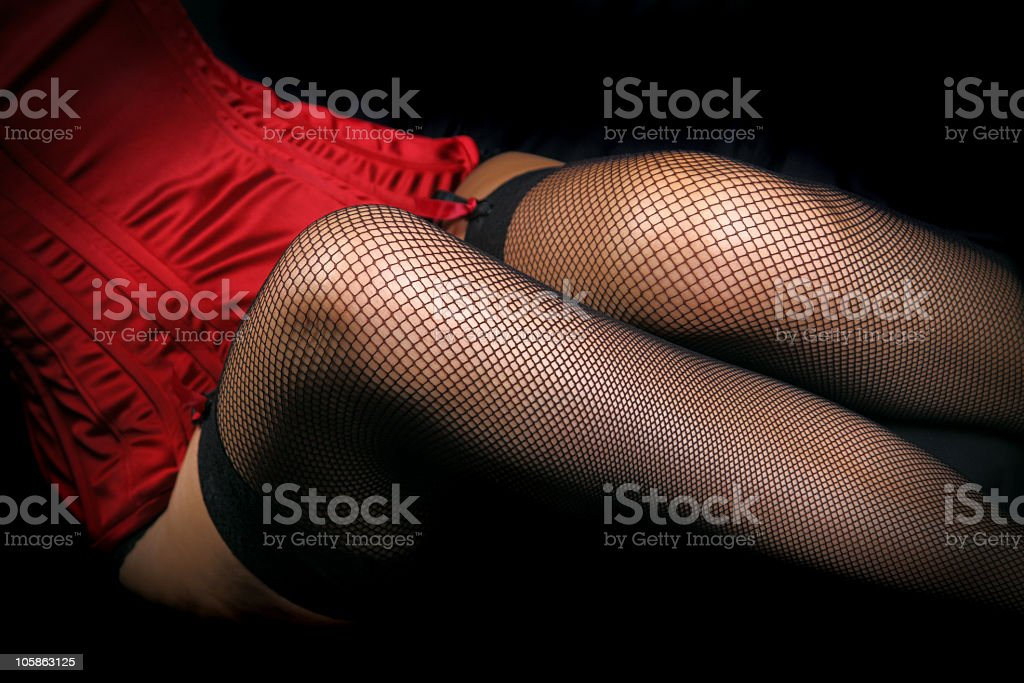 Close-up of a woman's legs in fishnet stockings and lingerie stock photo