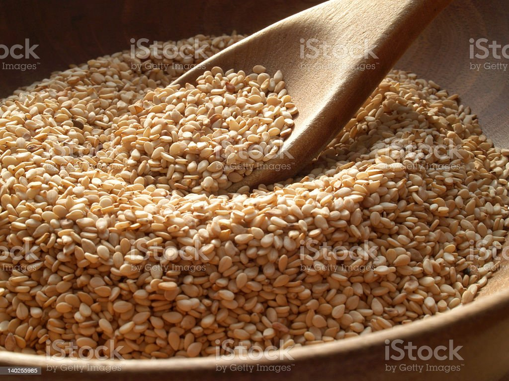 Close-up of a wooden spoon and bowl containing sesame seeds stock photo