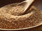 Close-up of a wooden spoon and bowl containing sesame seeds