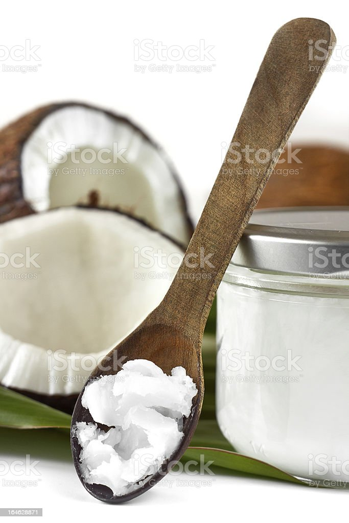 A closeup of a wooden spoon with a scoop of coconut oil stock photo