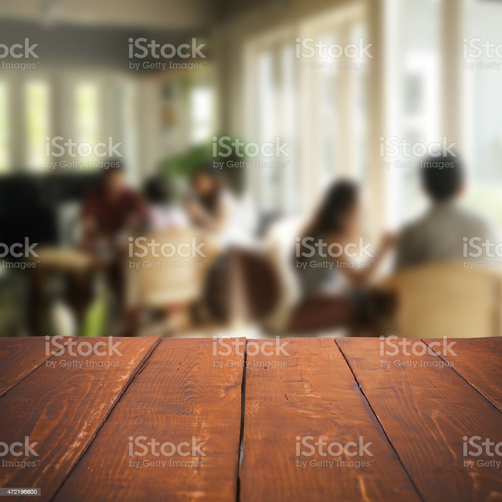 Close-up of a wooden table and people sitting at more tables stock photo