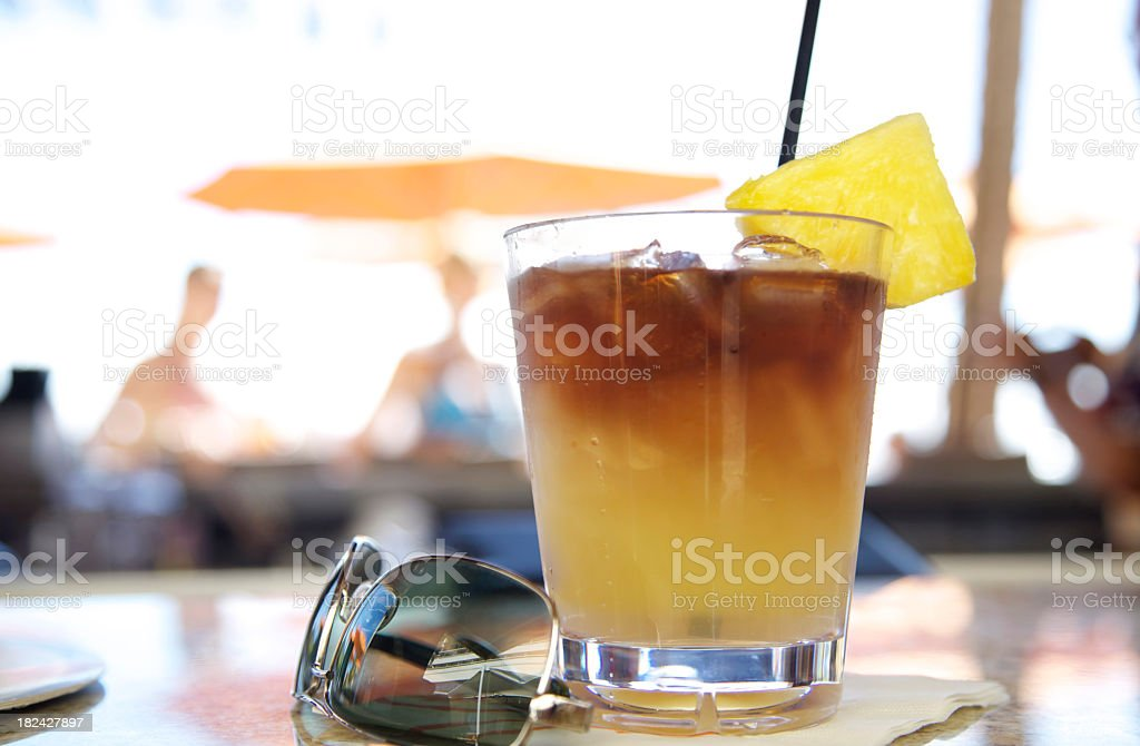 Close-up of a yellow brown drink next to pair of sunglasses stock photo