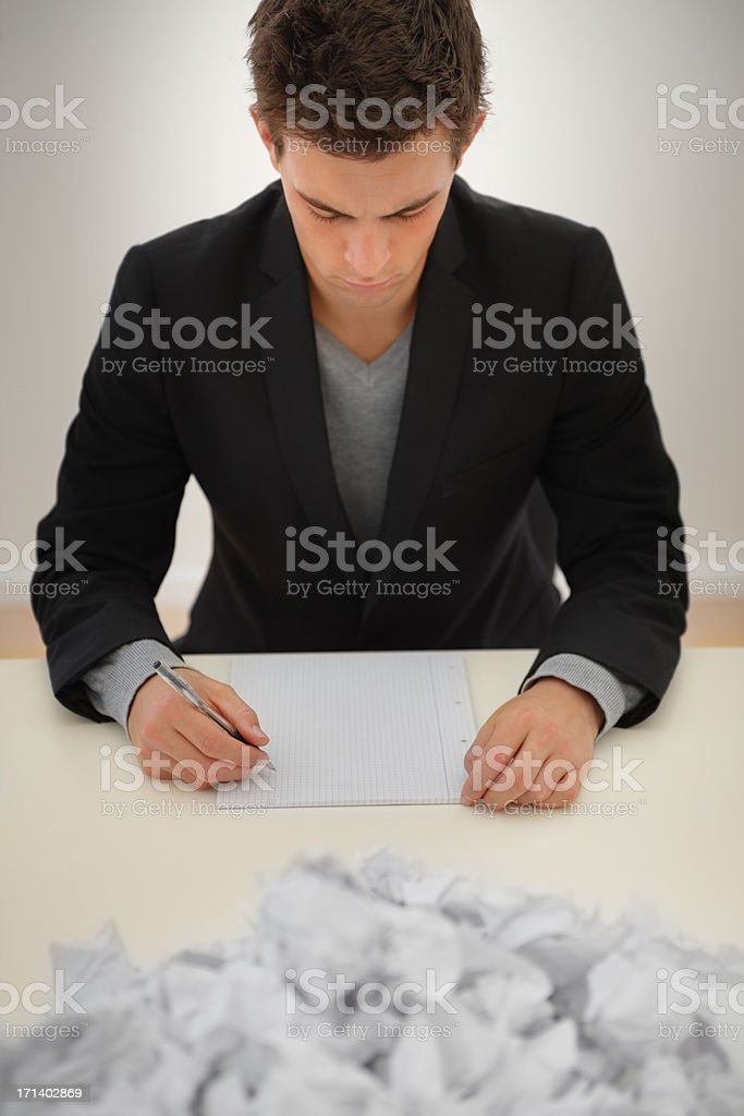 Closeup of a young business man writing with heap of papers in front royalty-free stock photo