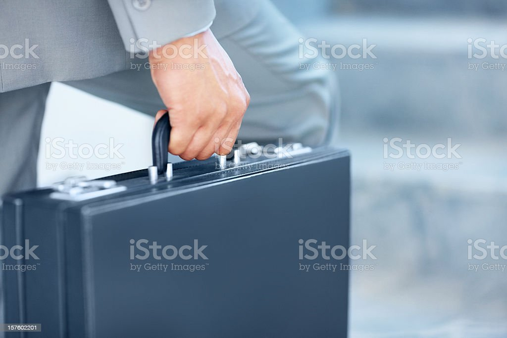 Close-up of a young businessman carrying briefcase stock photo