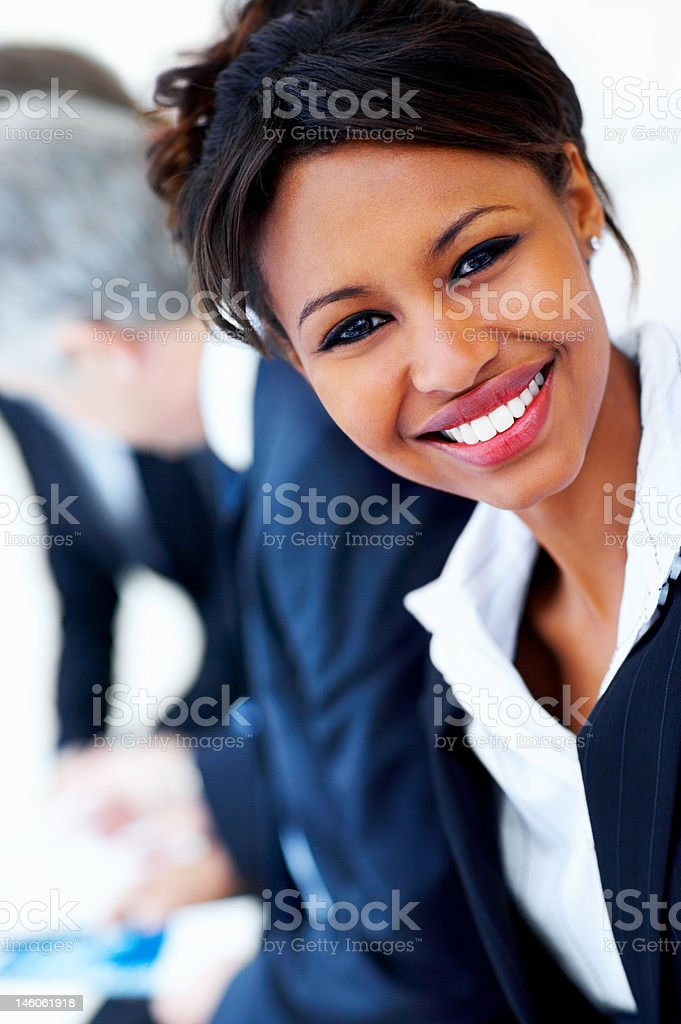 Close-up of a young businesswoman with colleagues in the background royalty-free stock photo