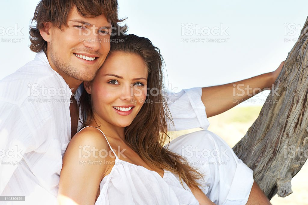 Close-up of a young couple sitting on the beach royalty-free stock photo