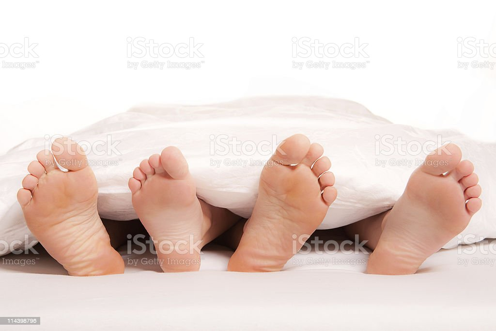 Close-up of  a young couple's feet on bed royalty-free stock photo