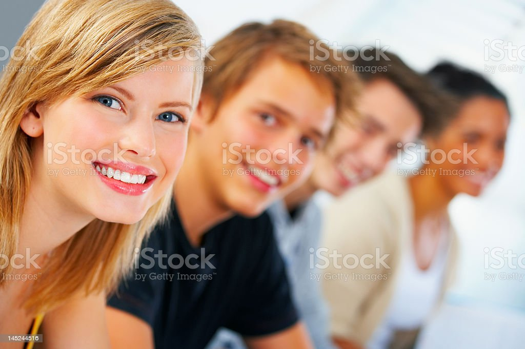 Close-up of a young female student smiling with her classmates royalty-free stock photo