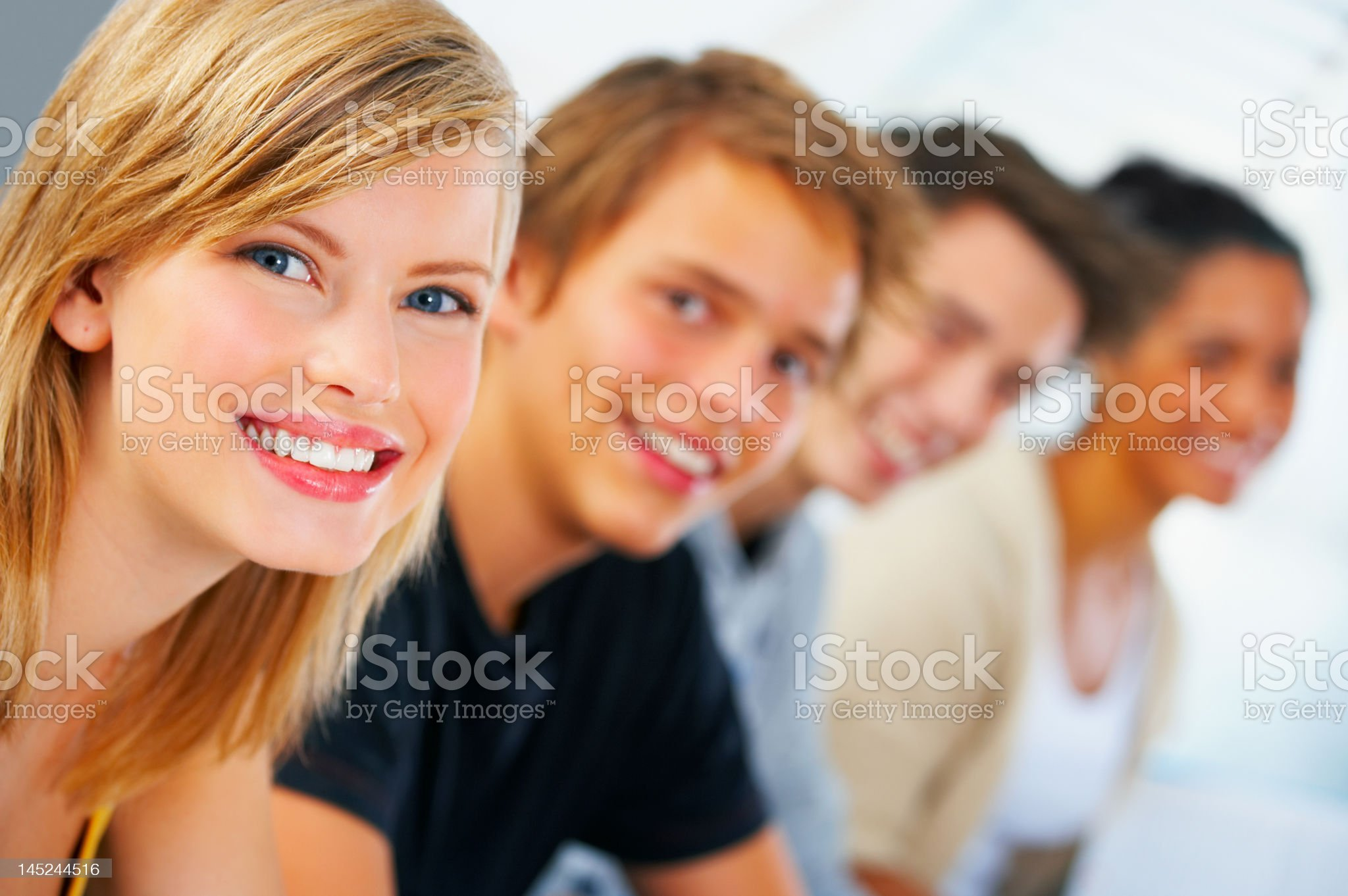 Close-up of a young female student smiling with her classmets royalty-free stock photo