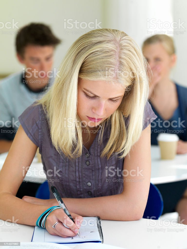 Closeup of a young girl writing in book royalty-free stock photo