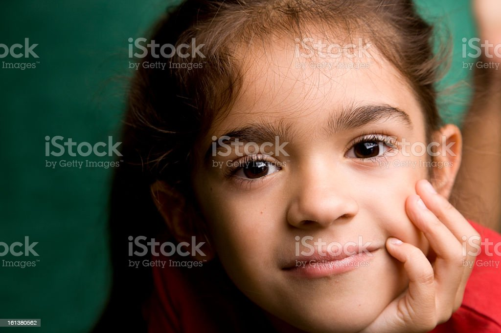 Close-up of a young hispanic school girl holding her cheek royalty-free stock photo