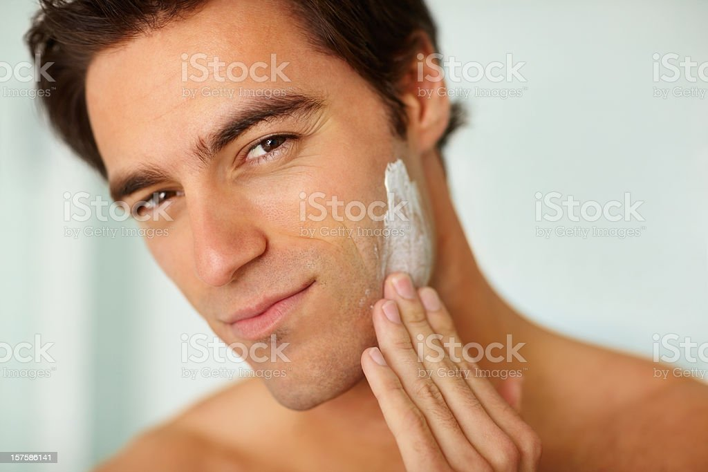 Closeup of a young man applying shaving cream to face royalty-free stock photo