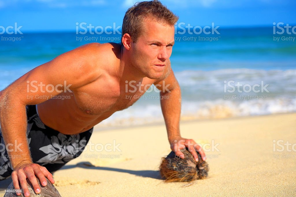 Close-up of a young man exercising on the beach royalty-free stock photo