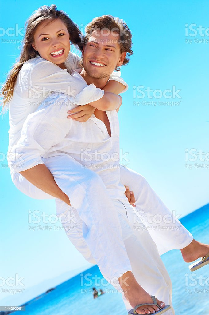 Close-up of a young man giving piggyback to his girlfriend royalty-free stock photo