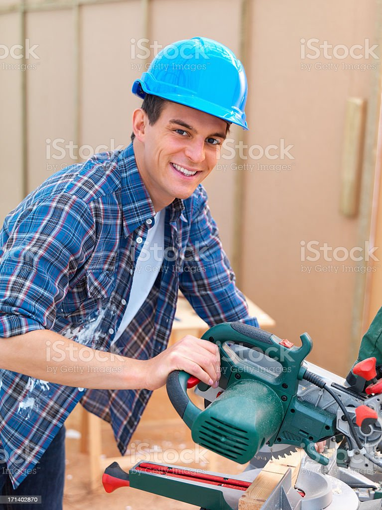 Closeup of a young man using an electric saw royalty-free stock photo