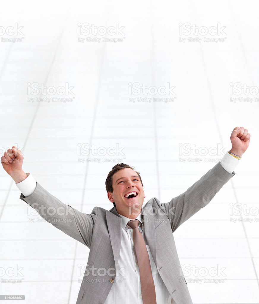 Close-up of a young successful businessman laughing with arms raised royalty-free stock photo