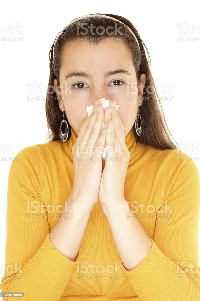 Close-up of a young woman blowing her nose stock photo