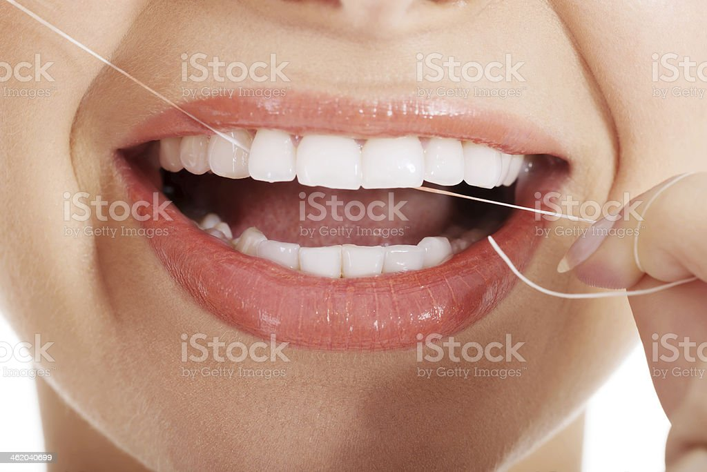 Closeup of a young woman flossing her teeth stock photo